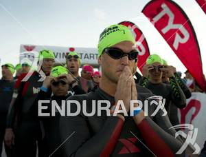 An age-grouper takes a moment to himself before entering the water  for the swim start at Ironman St. George in St. George, Utah May 5, 2012.