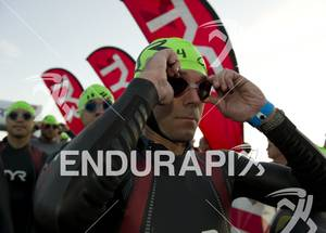 An age-grouper adjusts his goggles before entering the water  for the swim start at Ironman St. George in St. George, Utah May 5, 2012.