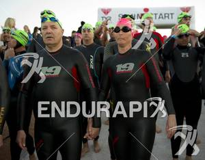 An age-group couple walks hand-in-hand as they ready to enter the water  for the swim start at Ironman St. George in St. George, Utah May 5, 2012.