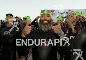 An age-grouper flashes a smile and gives a thumbs up before entering the water  for the swim start at Ironman St. George in St. George, Utah May 5, 2012.