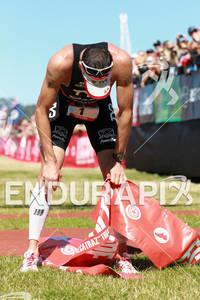 Andy Potts takes a minute to catch his breath after winning at the 2012 Escape from Alcatraz Triathlon on June 10, 2012 in San Francisco, CA