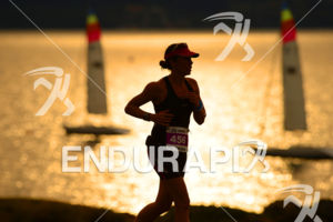 Age Group athlete running past scenic Lake Taupo at sunset, 2013 Ironman New Zealand, Taupo New Zealand, March 2 2013.