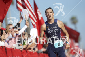 Matthew McElroy arrives at the finish at the 2018 Escape Surf City Triathlon on April 22, 2018 in Huntington Beach, CA.