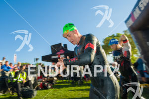 Older male athlete looking strong exiting the water at the 2018 Ironman Wisconsin on September 09, 2018 in Madison, WI.
