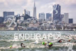 Athletes swim with the San Francisco skyline in view at…