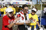 An age-group athlete is assisted by volunteers at the finish…
