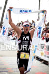 Andy Potts raises finish line tape at the Rohto Ironman…