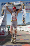 Joe Gambles holds up finishing tape at the 2011 Ironman…