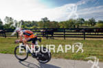 Patrick Evoe (USA) bikes past one of the many horse…