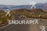 Ironman athletes on bike course through the desert at the…