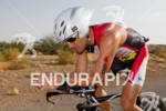 Craig Alexander (AUS) on bike through the desert while competing…