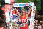 Chrissie Wellington crosses the finish line celebrating her fourth win…