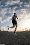 Age group athlete before sunset in the run portion of…