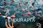 Athletes wait in water for start of swim.