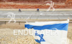Triathletes in the Arava Valley front of the flag of…