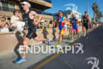 Group of elite men run along side crowds lined the…