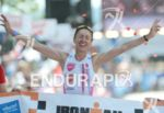 Erica Csomor celebrating at the finish line of the Ironman…
