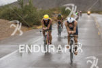Sebastian Kienle riding by Craig Alexander in the rain at…