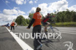 Age groupers pass an an aid station on the bike…