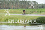 Age group athlete passes a lake during the bike leg…