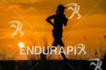 age group athlete at sunset during the run leg at…