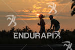 Triathletes running at the sunset during the run portion of…
