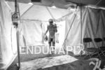 Lionel Sanders enters the bike to run transition tent at…