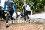 Age group athletes walk in the rain to the the…