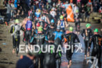 Age group athletes fill the beach as they exit the…