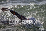 The pros swim through rough water during the swim leg…