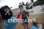 Triathletes have sun screen applied in the transition area at…