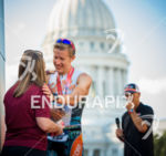Clay Emge embraces his wife after finishing first at the…