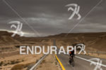 Athletes bike on the challenging course at the Israman triathlon…