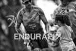 Pro triathlete Chris McDonald passes an aid station at mile…